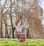 Pensionären i rullstol som gör en gest lycka parkerar in Royaltyfri Fotografi