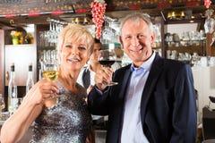 Pensionären kopplar ihop på bommar för med exponeringsglas av wine räcker in Royaltyfri Bild