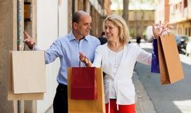 Pensionären med den mogna kvinnan som har shopping, turnerar i stad Arkivfoto