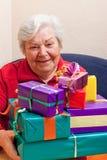 Pensionären sitter och får eller ger många gåvor Royaltyfri Fotografi
