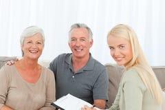 Pensionärer med doktorn som hemma ser kameran Arkivbild
