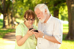 Pensionärer och ilar telefoner Royaltyfri Fotografi