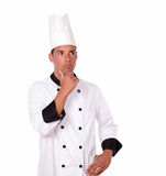 Pensive 20-24 years male chef standing. Portrait of pensive 20-24 years male chef on white uniform standing on isolated background - copyspace stock photos