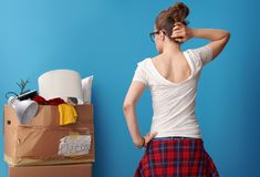 Pensive active woman looking at untidy cardboard box on blue Royalty Free Stock Images
