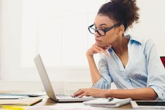 Pensive business woman working on laptop at office Stock Photo