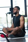 Pensive african american sportsman in earphones using smartphone and looking away while sitting on yoga mat. In gym royalty free stock photos