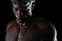 Pensive african male swimmer. Young african male swimmer looking down in thought. Close-up image of pensive young man with swimming goggles and wet body on black Stock Photos