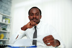 Pensive african man sitting at the table Stock Photography