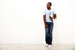 Pensive african man standing with laptop. Over white background Royalty Free Stock Photography