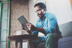 Pensive African man using tablet for video conversation while relaxing on sofa in modern office.Concept of young. Business people working at home.Blurred Stock Photos