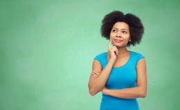 Pensive afro american  woman over green chalkboard Royalty Free Stock Images