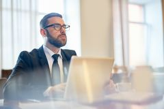 Pensive analyst. Pensive businessman contemplating in front of laptop while organizing work stock photo