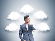 Pensive Asian businessman, thought clouds Stock Photos