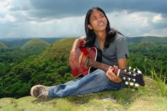 Pensive Asian hippie w guitar Royalty Free Stock Photos