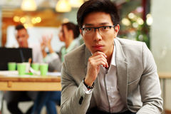 Pensive asian man sitting in office Royalty Free Stock Image