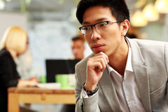 Pensive asian man sitting in office, Royalty Free Stock Photo