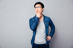 Pensive asian man standing over gray background Royalty Free Stock Image