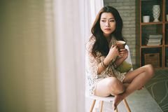 Deep in thoughts. Pensive Asian young woman drinking cup of hot coffee and looking through the window of her room Royalty Free Stock Photo