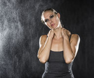 Pensive Athletic Woman Holding her Neck. Half Body Shot of an Athletic Young Woman Holding her Neck While Looking Into the Distance with Pensive Facial Royalty Free Stock Photography
