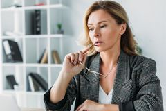 Pensive attractive businesswoman biting glasses. In office stock image