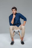 Pensive attractive casual young man sitting on chair Stock Images