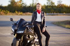 Pensive attractive woman has thoughtful gaze into distance, dressed in leather jacket, red bandana, has outdoor rest after driving royalty free stock image