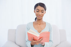 Pensive attractive woman sitting on cosy sofa reading a book Stock Photography