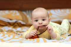 Pensive baby boy sucking beads Stock Photos