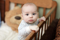 Pensive baby in cot Royalty Free Stock Photography