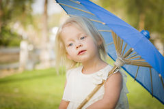 Pensive Baby Girl Holding Parasol Outside At Park Royalty Free Stock Images