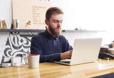 Pensive barman working on laptop at bar counter. Thoughtful bearded barman with laptop at bar counter. Hipster bartender working with computer. Online purchase Stock Photo