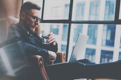 Pensive bearded businessman working at the modern loft office.Man sitting in vintage chair,holding in hands glass of. Water,using contemporary notebook royalty free stock photo