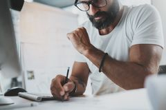 Pensive bearded designer wearing eye glasses and white tshirt, working at modern loft studio-office.Man drawing scetches. Blurred background. Horizontal.Cropped Stock Photo