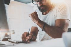 Pensive bearded designer wearing eye glasses and white tshirt, working at modern loft studio-office.Man drawing scetches. Blurred background. Horizontal.Flares stock photos