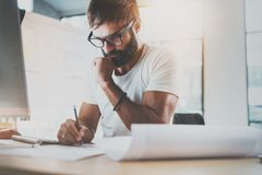 Pensive bearded designer wearing eye glasses and white tshirt, working at modern loft studio-office.Man drawing scetches. Blurred background. Horizontal.Flares Stock Photography