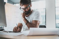 Pensive bearded designer wearing eye glasses and white tshirt, working at modern loft studio-office.Man drawing scetches. Blurred background. Horizontal royalty free stock photos