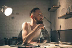 Pensive bearded male painting pictures Royalty Free Stock Photography