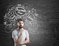Pensive bearded man and business plan sketch Royalty Free Stock Image