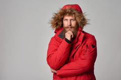 Pensive bearded man in red winter jacket Royalty Free Stock Photos
