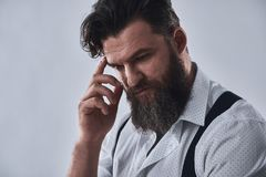 Pensive bearded man. In shirt with suspenders is thinking, on a light background stock image
