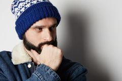 Pensive Bearded man Wearing blue jeans jacket and beanie on white background. Studio shot. Pensive Bearded man Wearing blue jeans jacket and beanie on white royalty free stock images