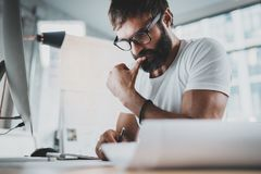 Pensive bearded man wearing eye glasses and white tshirt, working at modern loft studio-office.Blurred background stock photos