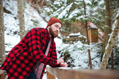 Pensive bearded young man standing in winter forest Royalty Free Stock Photos