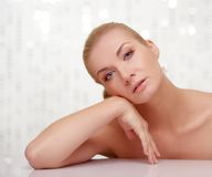 Pensive beautiful blond woman behind table Stock Photography