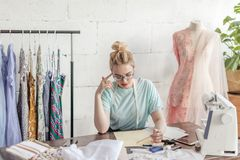 Fashion designer at work. Talanted dressmaker drawing sketch at her workspace. Pensive beautiful blonde dressmaker in fashion atelier in stylish eyeglasses and stock photos