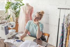 Fashion designer at work. Talanted dressmaker drawing sketch at her workspace. Pensive beautiful blonde dressmaker in fashion atelier in stylish eyeglasses and stock image