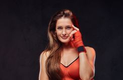 Pensive Beautiful Brunette Female Boxer In Sports Bra With Bandaged Hands. Isolated On Dark Textured Background. Royalty Free Stock Image