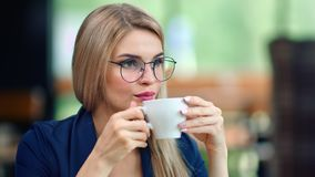 Pensive beautiful business woman drinking coffee from cup relaxing enjoying break medium close-up. Adorable young European female in fashion glasses thinking stock footage