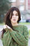 Pensive beautiful young woman with green sweater, outdoor. Stock Image