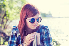 Pensive beautiful young woman in sunglasses with book Royalty Free Stock Photos